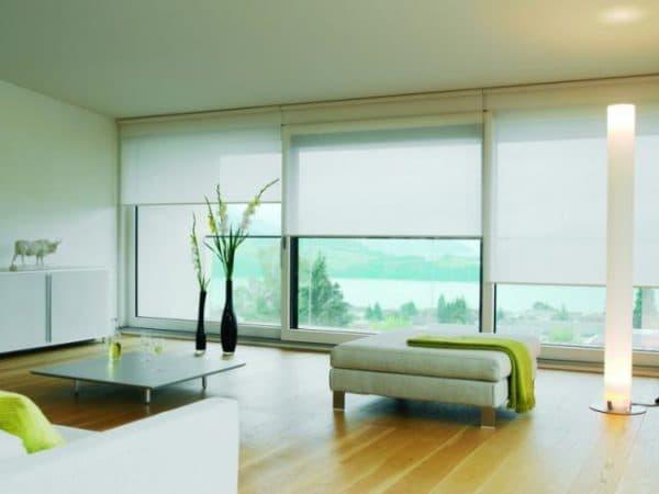 Большие окна – это очень красиво, но эта красота создает такую проблему, как правильный подбор штор. Они должны защищать комнату от чрезмерного действия солнечных лучей и от посторонних глаз. Какие шторы подходят для больших окон? Виды Рулонные  Это приемлемый вариант для больших оконных проемов. Собой представляют широкие полотна, которые скручиваются в рулон над окном. В свою очередь есть несколько вариантов рулонных штор: кассетные, открытые, стандартные. Открытые можно установить на потолок или же стену, полотно же будет просто свисать. У кассетных имеется короб, который устанавливают с боковыми направляющими. Для просторных окон хорошо подходят. Кассетные закрывают все щели. Стандартные имеют струны, которые зафиксируют полотно в определенном направлении.  Для крепления рулонных штор на окна нужно найти место для установки декоративного короба. Кассетные рулонные чаще других вешают на такие окна. Эта система будет лучше других смотреться, сливаясь с проемами. Установить их можно, просверлив дыры в стене, или же можно повесить на строительный скотч. Но помните: скотч не является практичным в применении. Самим устанавливать рулонные шторы не рекомендуется, пусть это сделает специалист, во избежание повреждения стеклопакетов.  Какие материалы используют для штор? Их изготавливают из ткани, полиэстера и соломки. При изготовлении из ткани используют специальный раствор, которым и пропитывают эту ткань. Он защитит шторы от пыли, влаги, от выгорания на солнце. Также есть ткани, которые не горят. Их чаще используют для больших окон в детском саду и в школе. Рулонные сейчас стали все больше дополнять декоративными элементами. По желанию ткань может быть сделана из водонепроницаемой основы. Такой вид подойдет для больших окон спальни. Цвет может быть любым: все зависит от личных предпочтений.  Управлять рулонными шторами можно с помощью нескольких механизмов. Самое простое - это управление с помощью цепочки. Ткань будет наматываться на рулон. Если механизм пружинный, то 